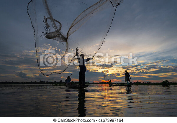 Silhouette of Fisherman on fishing boat with net on the lake at sunset, Thailand - csp73997164