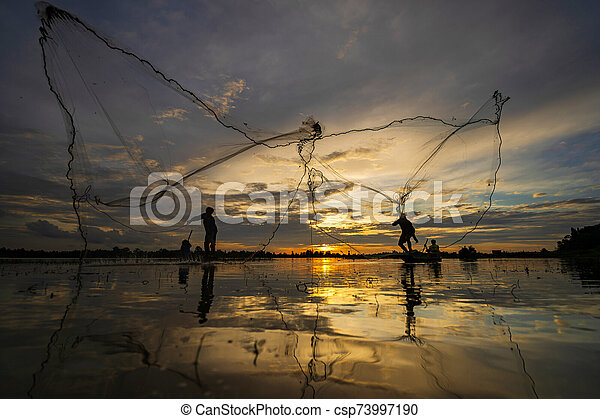 Silhouette of Fisherman on fishing boat with net on the lake at sunset, Thailand - csp73997190