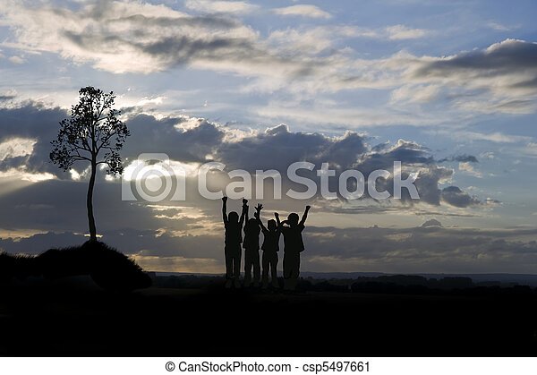 Silhouette of four young children against stunning sunset with s - csp5497661