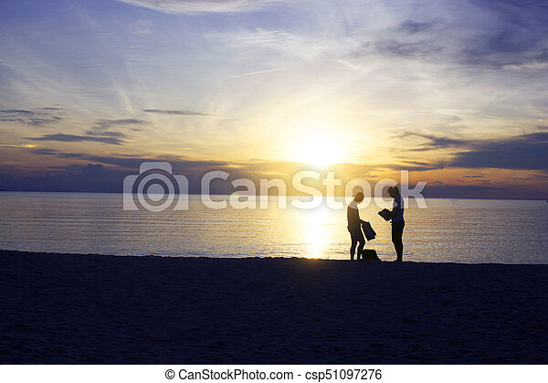 Silhouette of gay couple on the beach during sunset, Romantic sea with his love. - csp51097276