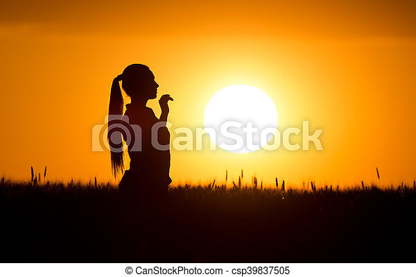 Silhouette of girl in wheat field - csp39837505