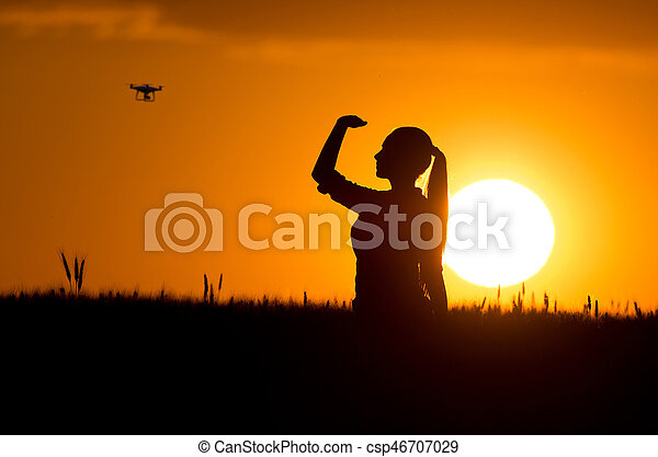 Silhouette of girl looking at drone - csp46707029