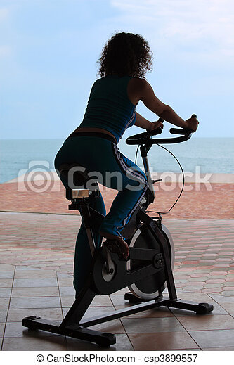 silhouette of girl on bicycle training apparatus outdoor - csp3899557