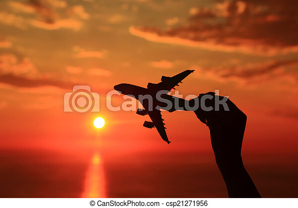 Silhouette of hand holding airplane miniature with sunset background  - csp21271956