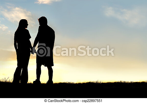 silhouette of happy couple holding hands and talking at sunset stock photo