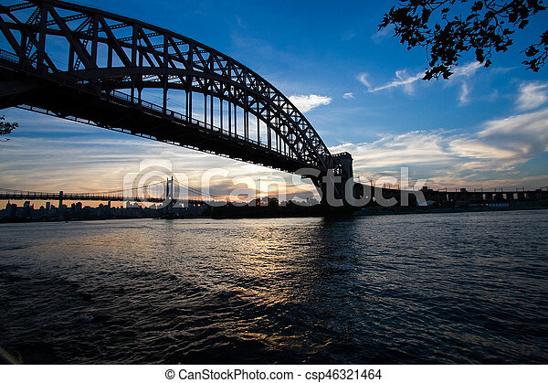 Silhouette of Hell Gate Bridge and Triborough bridge over the river, New York - csp46321464
