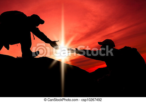 Silhouette of helping hand between two climber - csp10267492