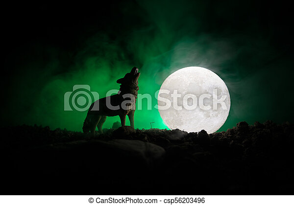 Silhouette of howling wolf against dark toned foggy background and full moon or Wolf in silhouette howling to the full moon. Halloween horror concept. - csp56203496