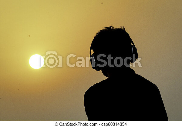 Silhouette of man with headphones on sunset sky background - csp60314354