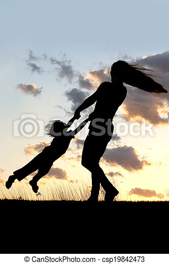 Silhouette of Mother Spinning and Dancing with Child at Sunset - csp19842473