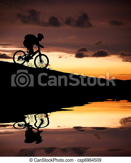 silhouette of mountain biker with Reflection and sunset - csp6964509