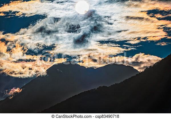 Silhouette of mountain range at orange cloudy sunset - csp83490718