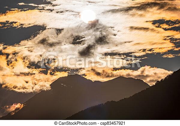 Silhouette of mountain range at orange cloudy sunset - csp83457921