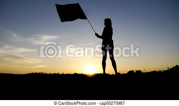 silhouette of people with flag on mountain top . - csp50270987