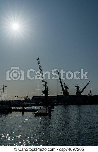 silhouette of port cranes in a large commercial port under a blue sky with a sun star - csp74897205