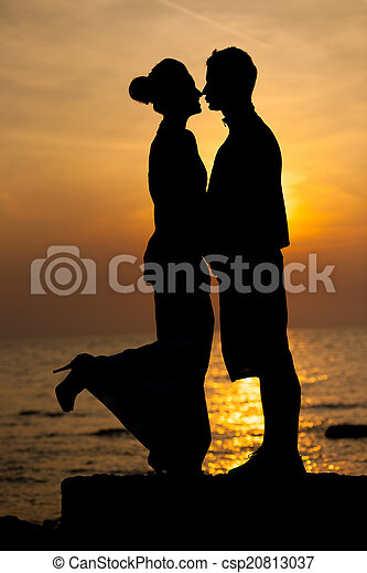 Silhouette of romantic couple on the beach at sunset - csp20813037