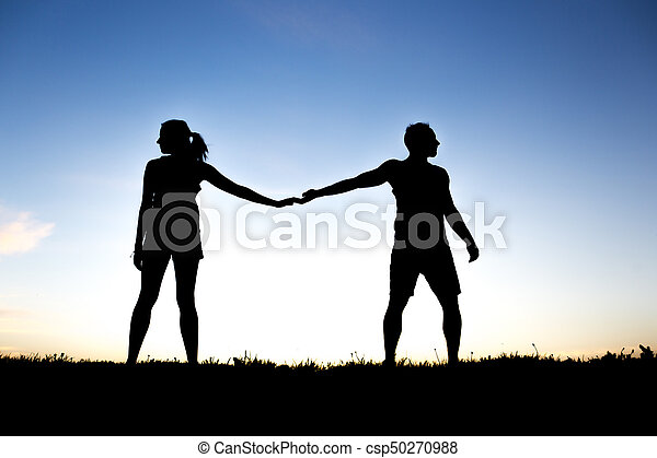 silhouette of romantic lovers with sunset on the back - csp50270988