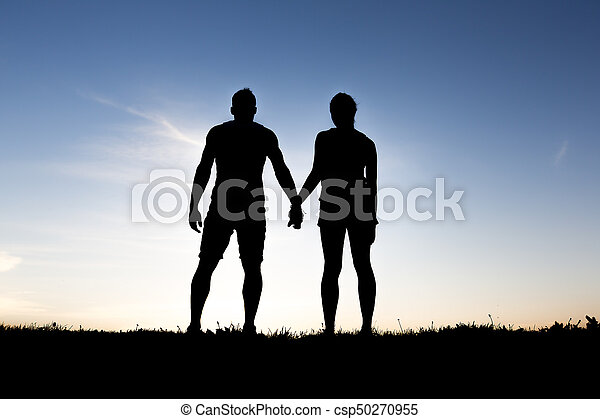 silhouette of romantic lovers with sunset on the back - csp50270955