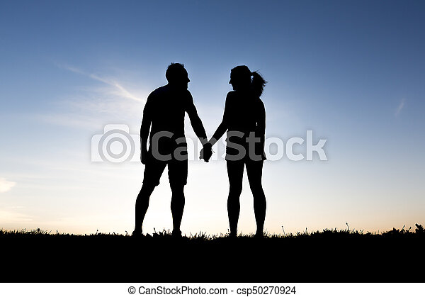 silhouette of romantic lovers with sunset on the back - csp50270924