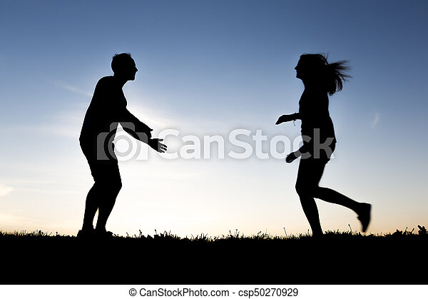 silhouette of romantic lovers with sunset on the back - csp50270929
