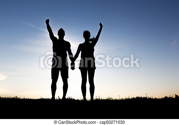 silhouette of romantic lovers with sunset on the back - csp50271030