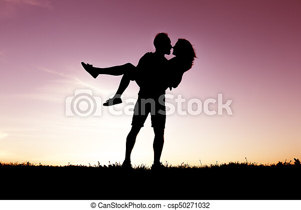 silhouette of romantic lovers with sunset on the back - csp50271032