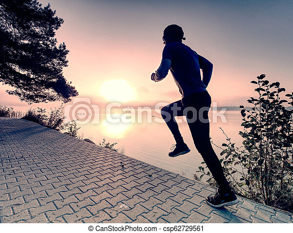 Silhouette of runner man along on the beach at sunset with sun - csp62729561