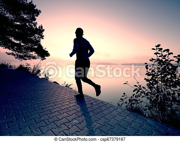 Silhouette of runner man along on the beach at sunset with sun - csp67379167
