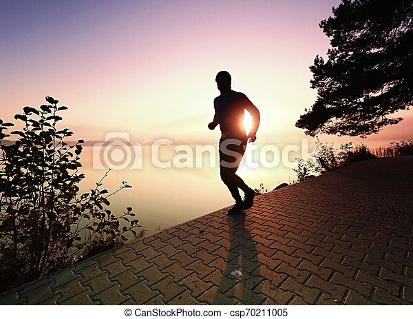 Silhouette of runner man along on the beach at sunset with sun - csp70211005