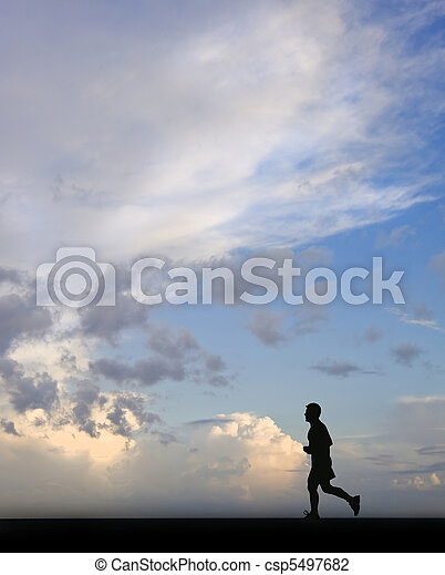 Silhouette of single male jogger against stunning blue sky - csp5497682