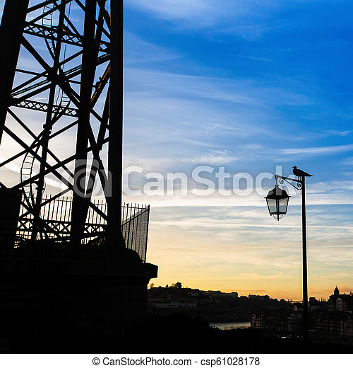 Silhouette of street lamp and the bird at evening time. Porto, Portugal. - csp61028178