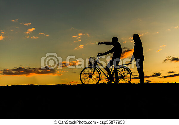 Silhouette of sweet couple in love happy time and bicycle in beautiful sunset - csp55877953