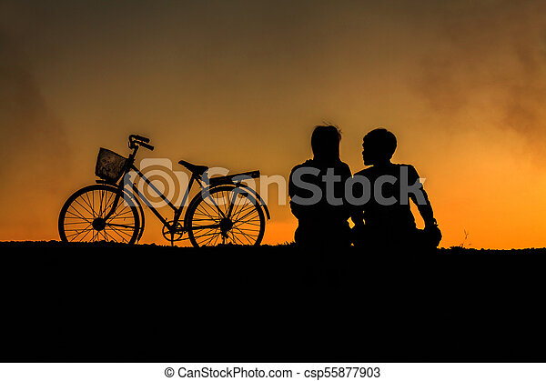 Silhouette of sweet couple in love happy time and bicycle in beautiful sunset - csp55877903