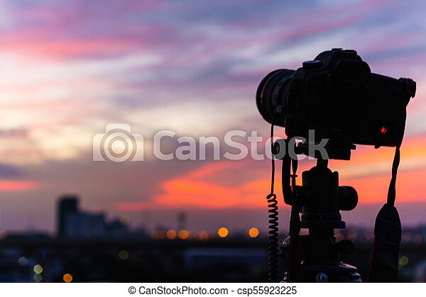 Silhouette of the camera is taking a photo of the twilight at the city - csp55923225