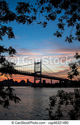 Silhouette of Triborough bridge over the river and buildings behind the branches with colorful sunset sky, New York - csp46321480