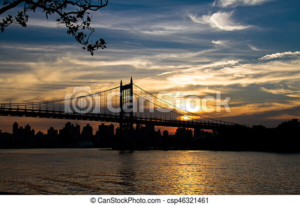 Silhouette of Triborough bridge over the river and city with sunset sky, New York - csp46321461