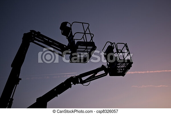 Silhouette of two cherry pickers against the evening sky - csp8326057
