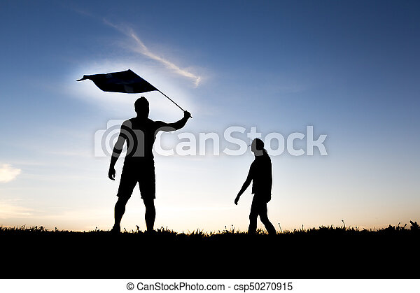 silhouette of two people at with sunset on the back with flag - csp50270915