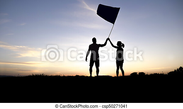 silhouette of two people at with sunset on the back with flag - csp50271041