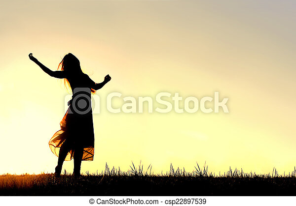 Silhouette of Woman Dancing and Praising God at Sunset - csp22897539
