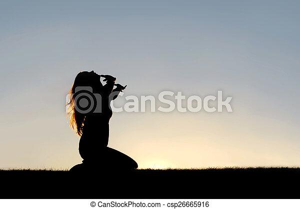 Silhouette of Woman Kneeling in Prayer and Surrender - csp26665916