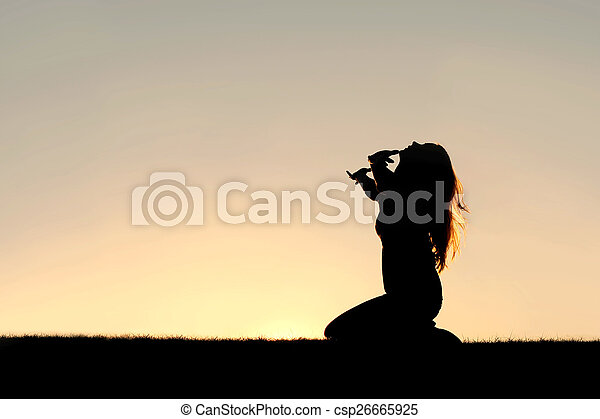 Silhouette of Woman Kneeling in Prayer and Surrender - csp26665925