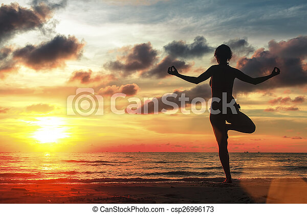 Silhouette Of Woman Standing At Yoga Pose On Beach During Amazing Sunset