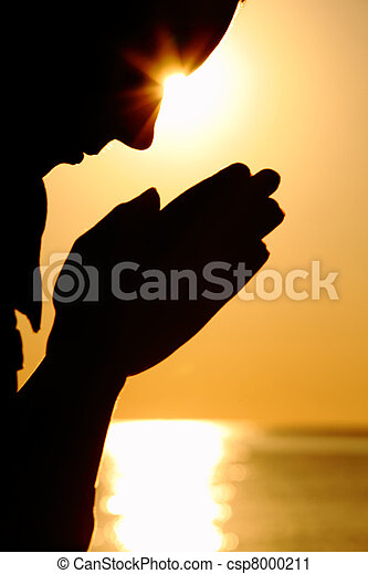 Silhouette of woman which sits near  sea opposite  sun and laid down hands before itself and prays - csp8000211