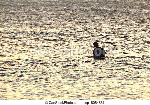 Silhouette of young fisherman in ocean at sunset - csp18054861