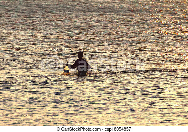 Silhouette of young fisherman in ocean at sunset - csp18054857