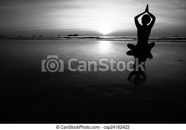 Silhouette of young woman practicing yoga on the sea beach. Black and white high contrast photography. - csp24162422