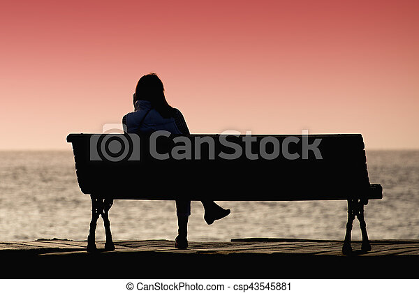 silhouette of young woman sitting alone on the bench in front of the