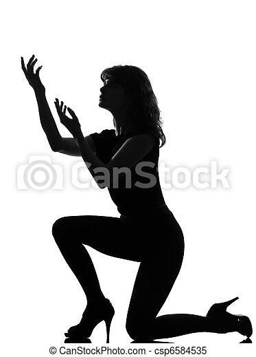silhouette woman kneel praying imploring - csp6584535