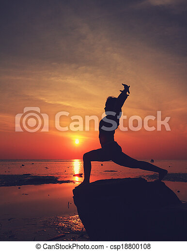 silhouette yoga girlthe beach at sunrise doing